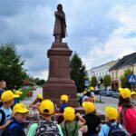 Grupa dzieci przed pomnikiem Tadeusza Kościuszki
