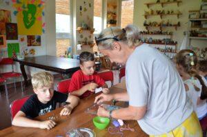 Dzieci przy stoliku na zajęciach plastycznych. Z grugiej strony kobieta, która coś im pokazuje