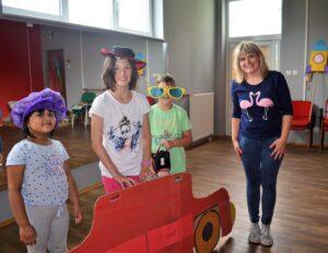 Troje dzieci i młoda kobieta. Każde z nicj ma na sobie element przebrania (śmieszne okulary, kolorową perukę, kapelusz)