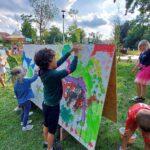 Park, lato. Dzieci przy dużym kartonie, maluja farbami kolorowy obrazek.