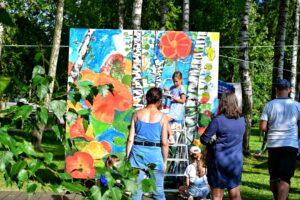 Kolorowy mural przedstawiający pnie brzóz i różnonbarwne kwait. Przy nim osoby malujące go i oglądające.