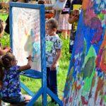 Kilkuletnie dzieci maluja na szklanej tablicy ustawionej w parku. Jest ładna pogoda, świeci słońce.