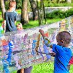 Kiluletni chłopiec maluje farbami na folii stretch rozciągniętej między pnami drzew w parku.