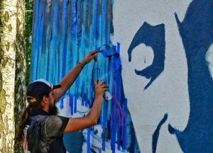 Młody mężczynza w czapce z daszkiem, ma długie włosy spięte w kucyk i brodę. Maluje muralfabrą w sprayu.