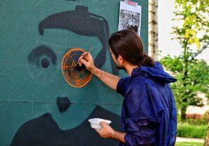 Młody mężczyzna ubrany w kombinezon ochronny z kapturem. Maluje mural.