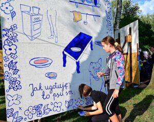 """Dwie dziewczynki przy wielkoformatowym obrazie, na którym są lelmentu wyposażenia kuchni, kwiaty i napis """"Jak ugotuję, to psu sm..."""""""