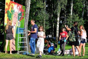 Park. Kilka osób maluje wielkoformatowy obraz przedstawiający kobietę w wianku z kwiatów na głowie.
