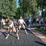 Trzy tancerki na macie rozłożonej w parku. Wokół przygladająca się im publiczność.