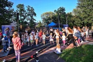 Park. Grupa dzieci ustawiona w duże koło. Trzymają się za ręce, tańczą.