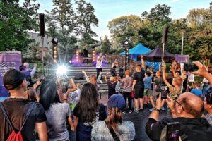 Park, letnia scena. Na niej dwóch mężczyzn i kobieta. Śpiewają. Przed sceną publiczność z uniesionymi rękami.