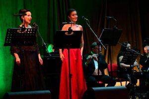 Dwie kobiety stoją na scenie. Przed nimi pulpity do nut i mikrofony. Z tyłu muzycy grający na instrumentach dętych. Kobiety śpiewają. Ubrane są w eleganckie, długie suknie.