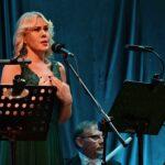 Kobieta o jasnych włosach, ubrana w zieloną, długą suknię. Przed nią mikrofon i pulpitdo nut.