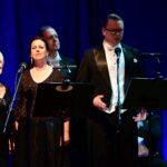 Czworo wokalistów. Dwie kobiety i dwóch mężczyzn. Są elegancko ubrani. Kobiety w długich wieczorowych sukniach, mężczyźni we frakach. Śpiewają do mikrofonów.