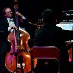 W tle mężczyzna grający na wiolonczeli. Z przodu skrzypek odwrócony tyłem do publiczności.