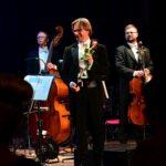 Czterech mężczyzn stoi na scenie. Jeden trzyma w ręce różę. Mężczyzna po prawej stoi przy wiolonczeli. Mężćzyzna po lewej trzyma w rękach skrzypce. Mężczyzna z tyłu przed sobą ma kontrabas.