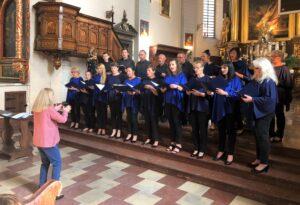 Kościół. Na stopniach ołtarza stoi grupa kobiet i mężczyzn. W rękach trzymają podkładki z nutami. śpiewają. Przodem do śpiewających stoi dyrygująca nimi kobieta.