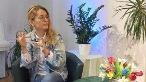 Kobieta o jasnych włosach, w okularach i kurtce dżinsowej. Siedzi na fotelu. Dłonie ułożone do migania PJM.
