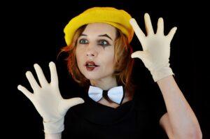Dziewczyna mim. Na głowie ma zółty beret. Dłonie w białych rękawiczkach trzyma tak, jakby opierała się o szybę. Patrzy przed siebie szeoko otwartym oczami.